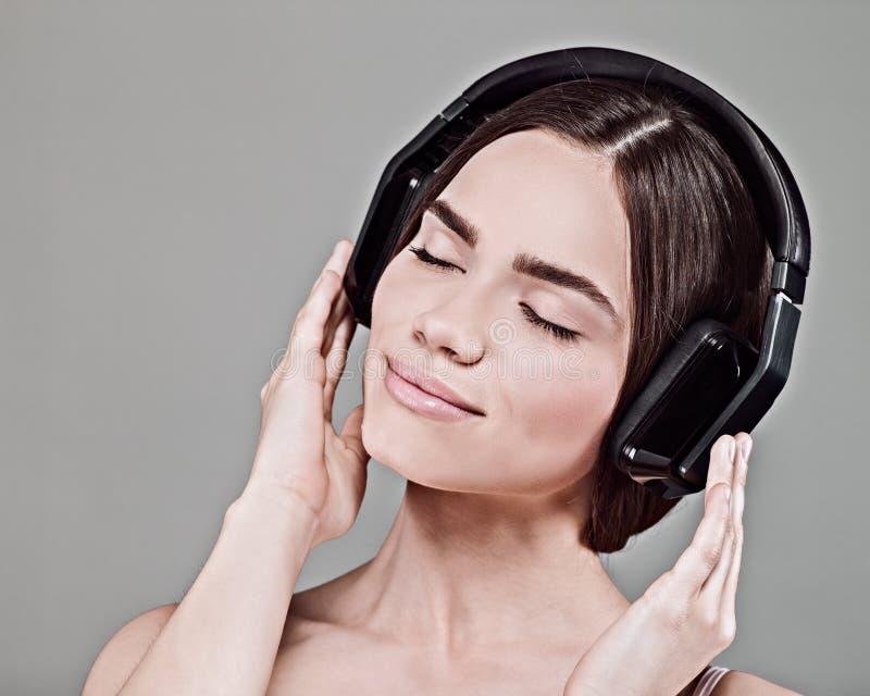 μουσική Η νέα ενήλικη γυναίκα ομορφιάς ακούει μουσική στοκ εικόνα με δικαίωμα ελεύθερης χρήσης