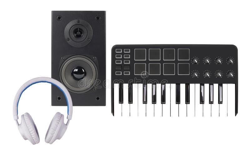 Μουσική και ήχος - μια περίφραξη μεγάφωνων, πληκτρολόγιο του MIDI και άσπρο ακουστικό απομονωμένος στοκ εικόνες