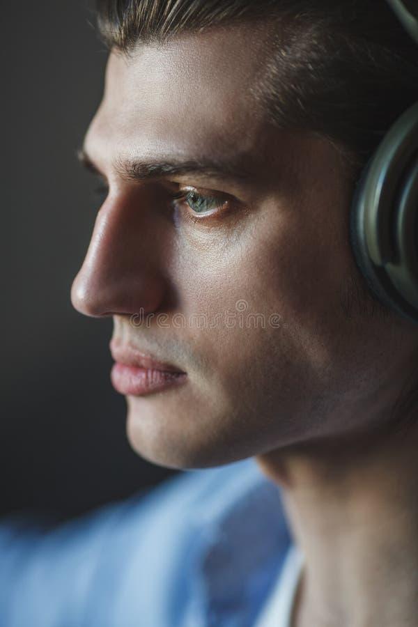 Μουσική στο μυαλό του Πορτρέτο του νεαρού άνδρα που φορά τα ακουστικά και που κοιτάζει μακριά στοκ εικόνες με δικαίωμα ελεύθερης χρήσης