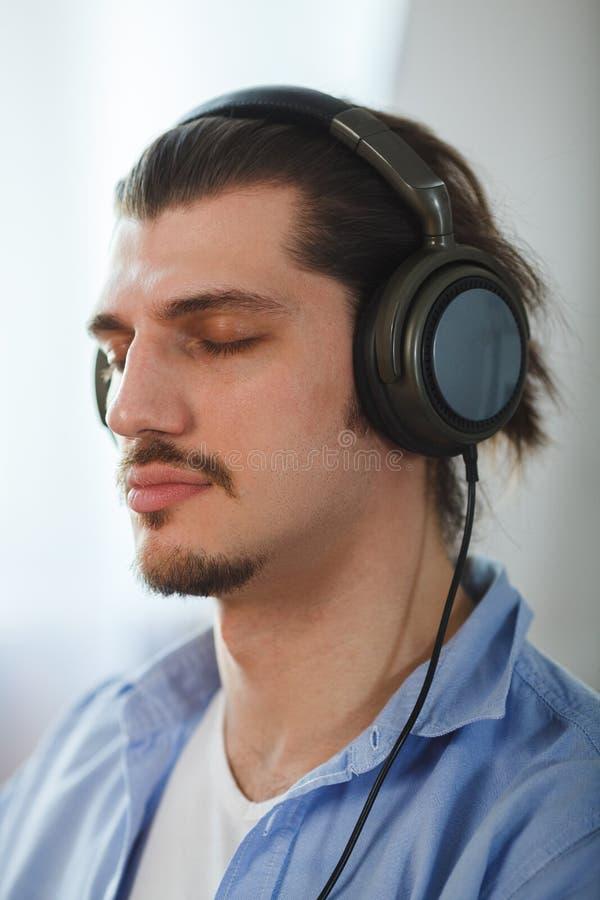 Μουσική στο μυαλό του Πορτρέτο του νεαρού άνδρα που φορά τα ακουστικά και τις ιδιαίτερες προσοχές στοκ φωτογραφία με δικαίωμα ελεύθερης χρήσης