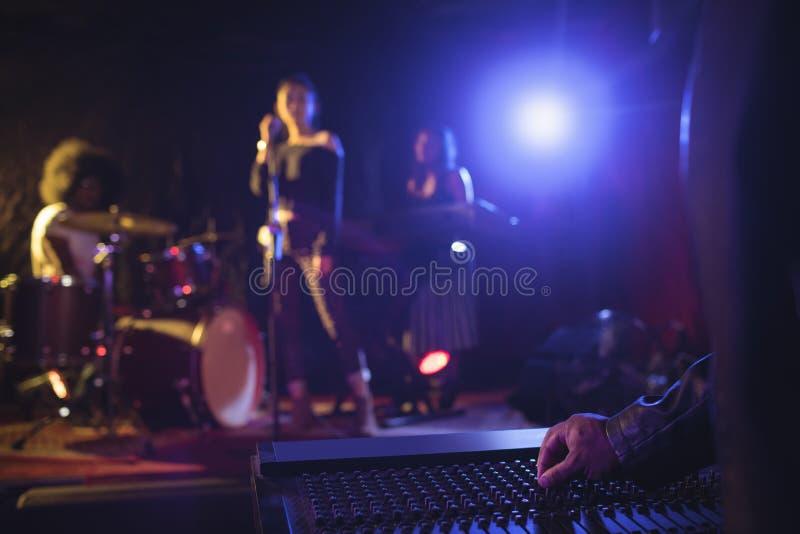 Μουσικοί που ενεργοποιούν τον υγιή αναμίκτη με τους εκτελεστές στο φωτισμένο στάδιο στο νυχτερινό κέντρο διασκέδασης στοκ εικόνες
