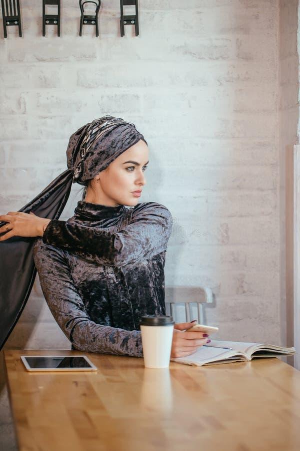 Μουσουλμανικές γυναίκες που κρατούν το smartphonephone σκέψη τις καλές μνήμες στοκ εικόνες με δικαίωμα ελεύθερης χρήσης
