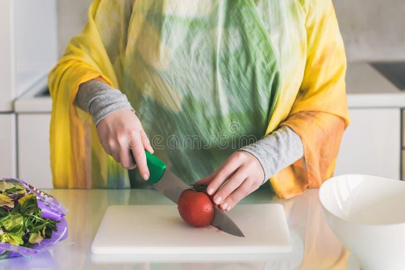 Μουσουλμανικές τεμαχίζοντας ντομάτες γυναικών στην κουζίνα στοκ φωτογραφία με δικαίωμα ελεύθερης χρήσης
