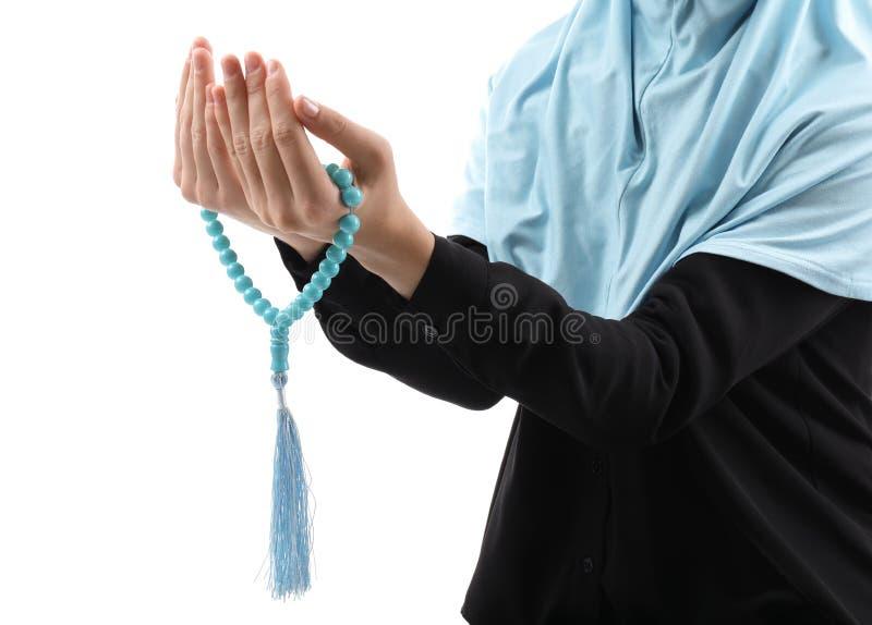 Μουσουλμανική γυναίκα με τις χάντρες που προσεύχεται στο άσπρο υπόβαθρο στοκ φωτογραφίες