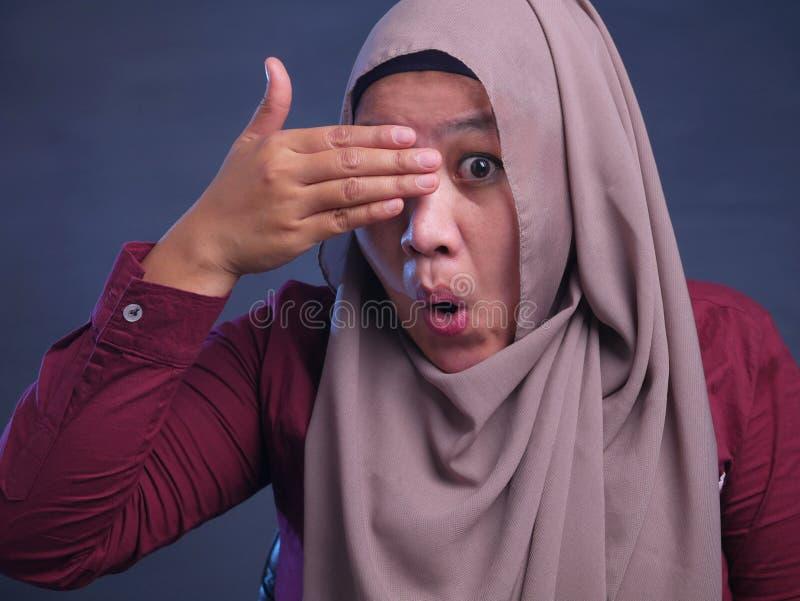 Μουσουλμανική γυναίκα που κρυφοκοιτάζει μέσω των δάχτυλών της στοκ εικόνες