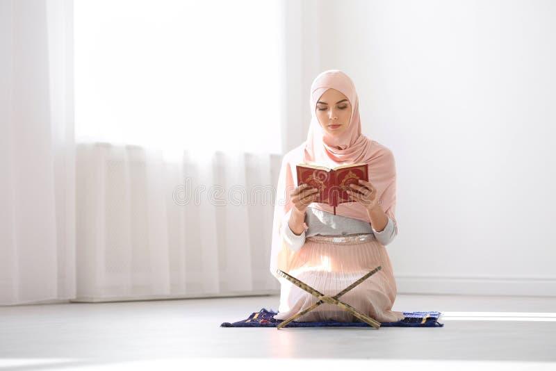 Μουσουλμανική γυναίκα στην ανάγνωση Koran hijab στοκ εικόνα