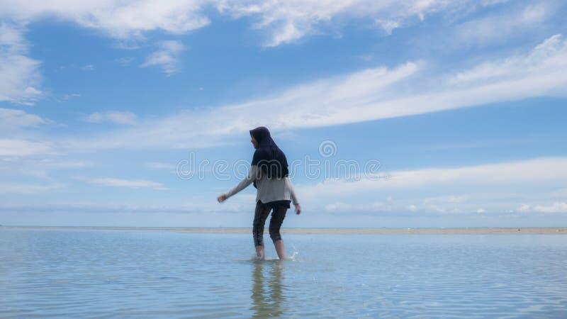 Μουσουλμανική γυναίκα στον προορισμό τουρισμού Halal, την παραλία και τον μπλε ωκεανό στοκ εικόνα