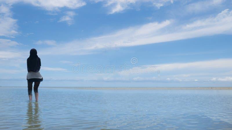 Μουσουλμανική γυναίκα στον προορισμό τουρισμού Halal, την παραλία και τον μπλε ωκεανό στοκ εικόνα με δικαίωμα ελεύθερης χρήσης