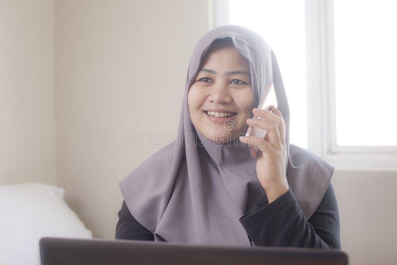 Μουσουλμανική επιχειρηματίας που μιλά στο τηλέφωνο στην αρχή, έκφραση χαμόγελου στοκ φωτογραφίες με δικαίωμα ελεύθερης χρήσης