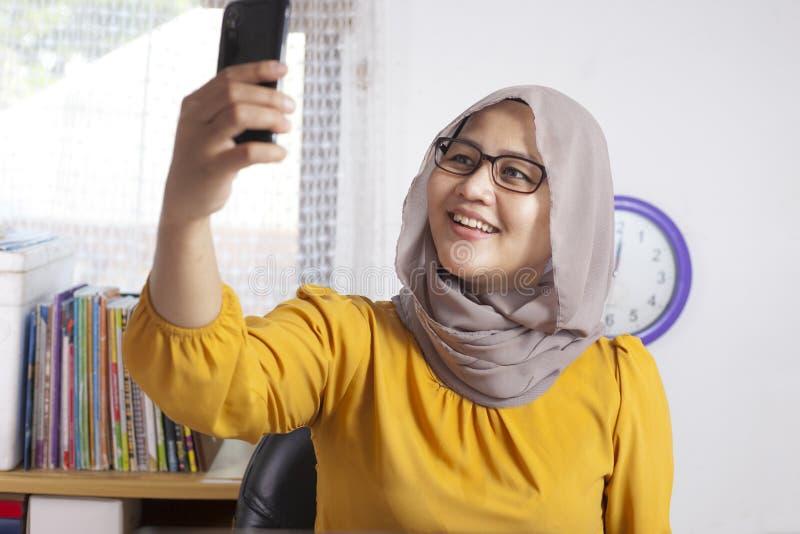 Μουσουλμανική επιχειρηματίας που παίρνει την εικόνα Selfie στο γραφείο στοκ φωτογραφίες με δικαίωμα ελεύθερης χρήσης