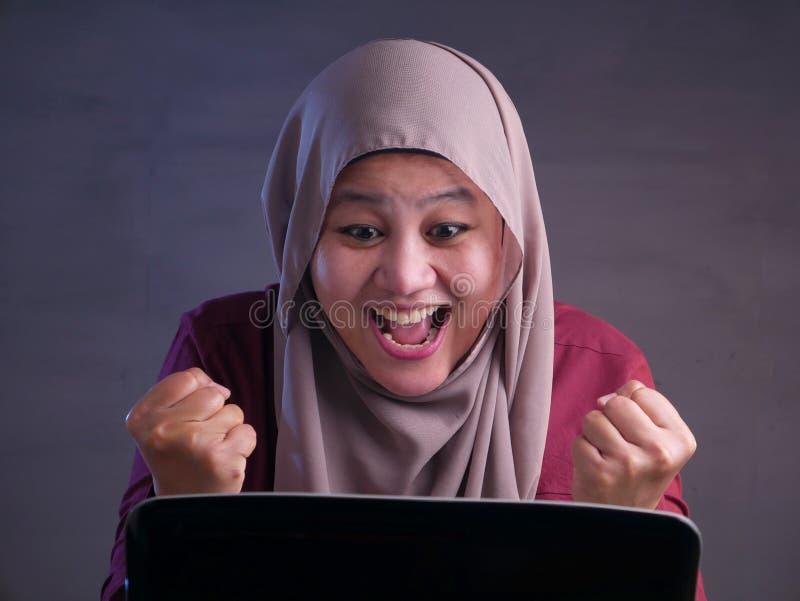 Μουσουλμανική κυρία Shows Winning Gesture, που λαμβάνει τις καλές ειδήσεις στο ηλεκτρονικό ταχυδρομείο της στοκ φωτογραφία με δικαίωμα ελεύθερης χρήσης