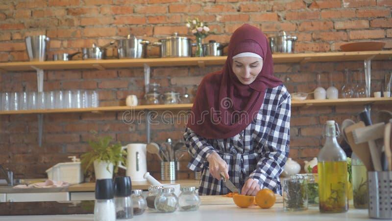 Μουσουλμανική νέα γυναίκα πορτρέτου στα λαχανικά περικοπών κουζινών στοκ εικόνες