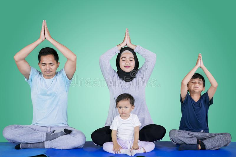 Μουσουλμανική οικογένεια που κάνει την άσκηση γιόγκας στο στούντιο στοκ φωτογραφίες