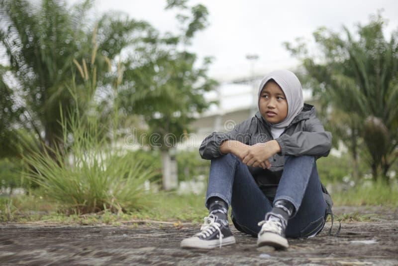 Μουσουλμανική συνεδρίαση κοριτσιών στο έδαφος στο πάρκο στοκ φωτογραφίες με δικαίωμα ελεύθερης χρήσης