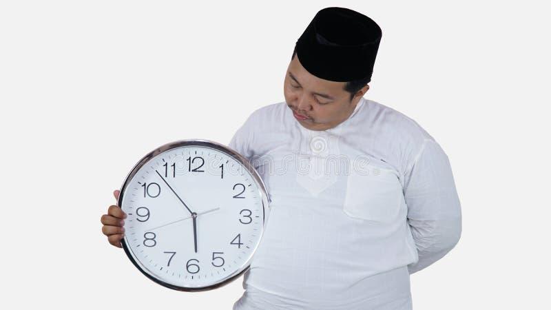 Μουσουλμανικός Ασιάτης με το υπέρβαρο μεγάλο στρογγυλό ρολόι στάσης και κρατήματος που περιμένει τη νηστεία σπασιμάτων το παχύ αγ στοκ εικόνες με δικαίωμα ελεύθερης χρήσης
