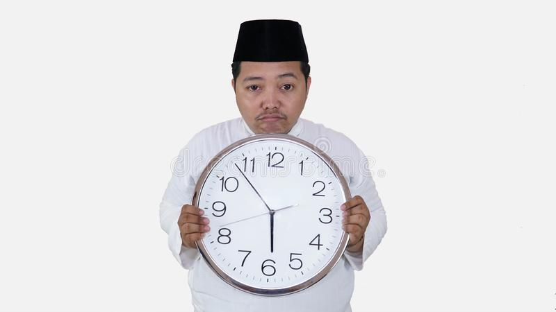 Μουσουλμανικός Ασιάτης με το υπέρβαρο μεγάλο στρογγυλό ρολόι στάσης και κρατήματος που περιμένει τη νηστεία σπασιμάτων το παχύ αγ στοκ εικόνα