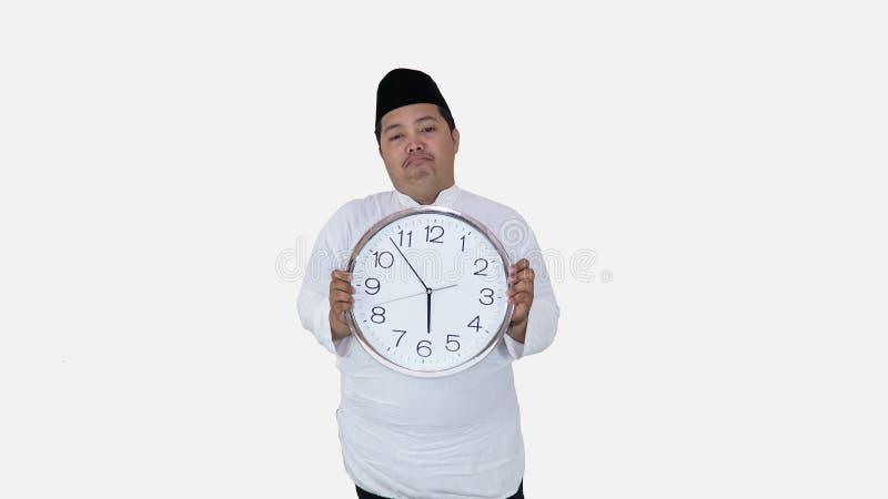 Μουσουλμανικός Ασιάτης με το υπέρβαρο μεγάλο στρογγυλό ρολόι στάσης και κρατήματος που περιμένει τη νηστεία σπασιμάτων το παχύ αγ στοκ φωτογραφία με δικαίωμα ελεύθερης χρήσης