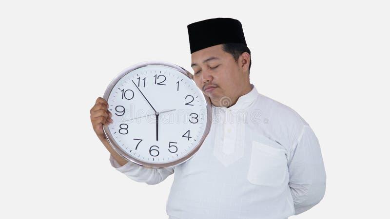 Μουσουλμανικός Ασιάτης με το υπέρβαρο μεγάλο στρογγυλό ρολόι στάσης και κρατήματος που περιμένει τη νηστεία σπασιμάτων το παχύ αγ στοκ φωτογραφίες