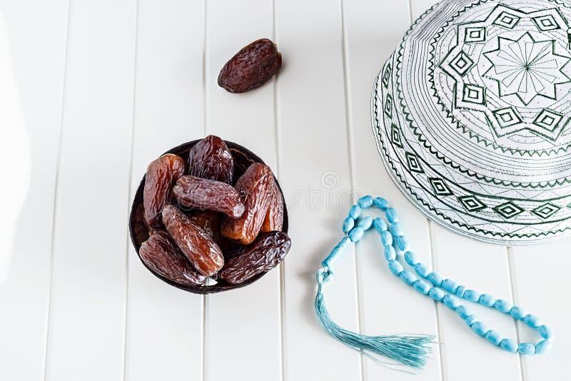 Μουσουλμανικός ισλαμικός σκούφος έννοιας πίστης taqiyah, μπλε rosary και ημερομηνίες medjul στοκ φωτογραφία με δικαίωμα ελεύθερης χρήσης