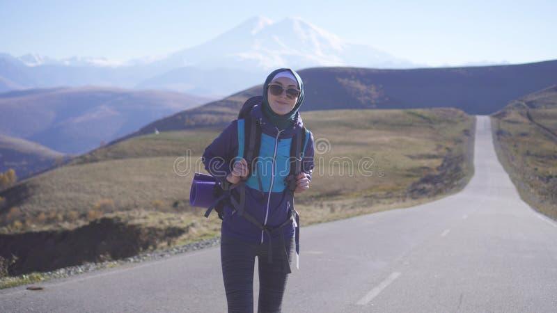 Μουσουλμανικός τουρίστας γυναικών με το σακίδιο πλάτης στην εθνική οδό στοκ φωτογραφία με δικαίωμα ελεύθερης χρήσης