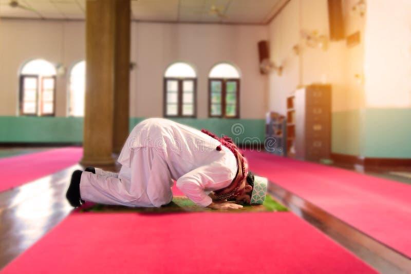 Μουσουλμανικό άτομο Ισλάμ στο φόρεμα συνήθειας που προσεύχεται στο μουσουλμανικό τέμενος στοκ φωτογραφία