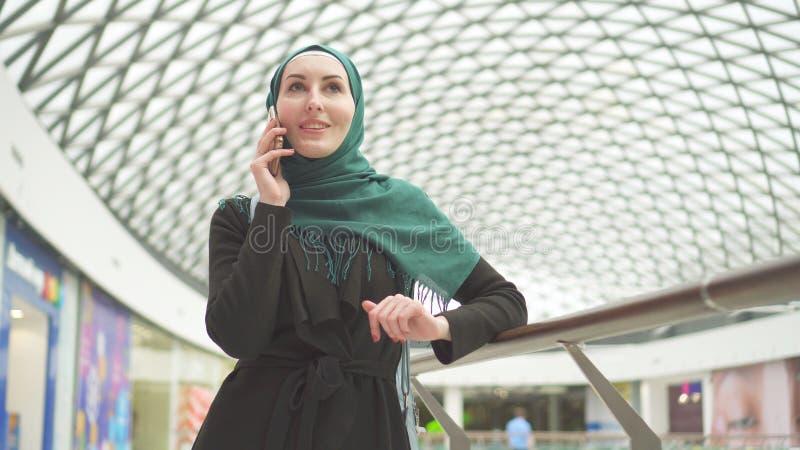 Μουσουλμανικό κορίτσι στο hijab που μιλά στο τηλέφωνο στο σύγχρονο εμπορικό κέντρο στοκ φωτογραφία με δικαίωμα ελεύθερης χρήσης