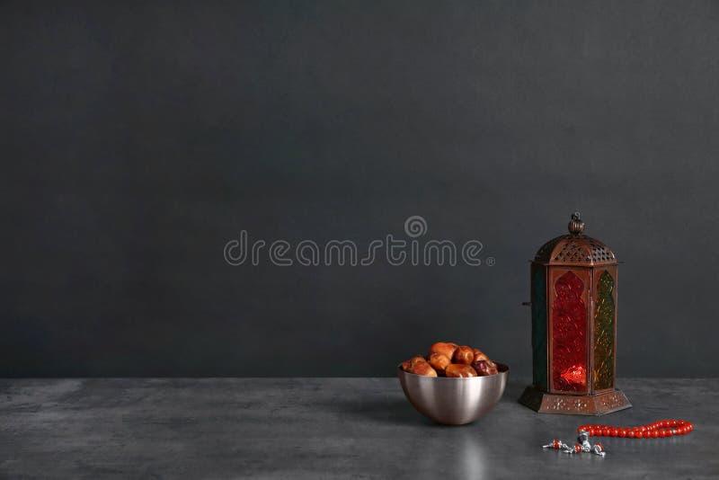 Μουσουλμανικό φανάρι Fanous, ξηρές ημερομηνίες και χάντρες προσευχής στον πίνακα στο σκοτεινό κλίμα στοκ φωτογραφίες