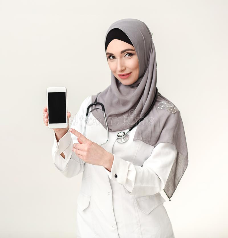 Μουσουλμανικό smartphone εκμετάλλευσης γιατρών γυναικών με την κενή οθόνη στοκ φωτογραφία με δικαίωμα ελεύθερης χρήσης