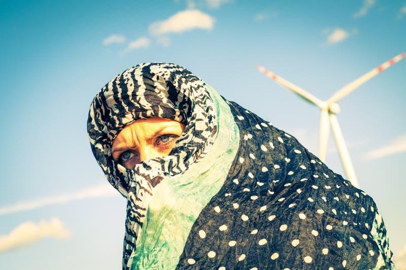 Μουσουλμανικά κορίτσι και windturbine στο υπόβαθρο στοκ εικόνες με δικαίωμα ελεύθερης χρήσης