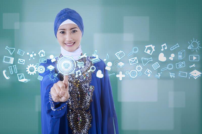 Μουσουλμανική επιχειρηματίας που χρησιμοποιεί τη σύγχρονη διεπαφή στοκ εικόνες