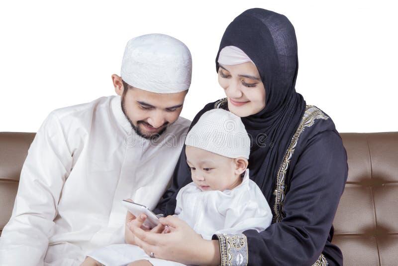Μουσουλμανική οικογενειακή συνεδρίαση στον καναπέ με το κινητό τηλέφωνο στοκ φωτογραφίες με δικαίωμα ελεύθερης χρήσης