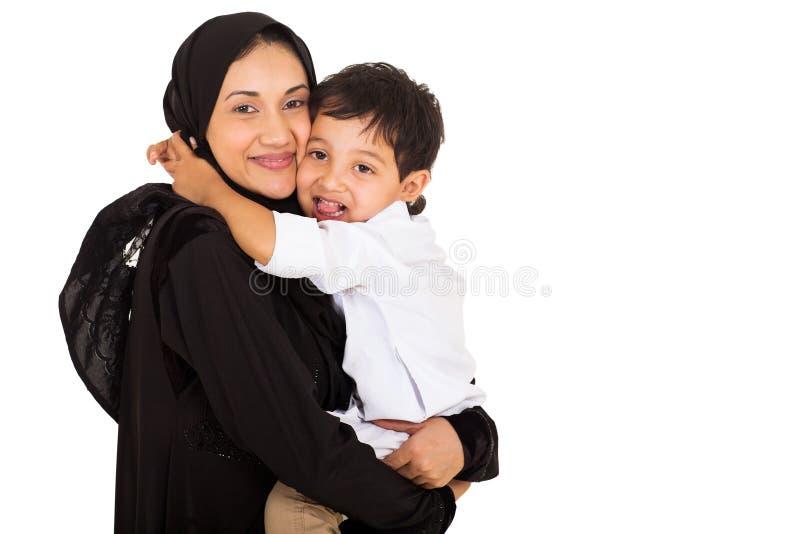 Μουσουλμανικό αγόρι που αγκαλιάζει τη μητέρα στοκ εικόνα