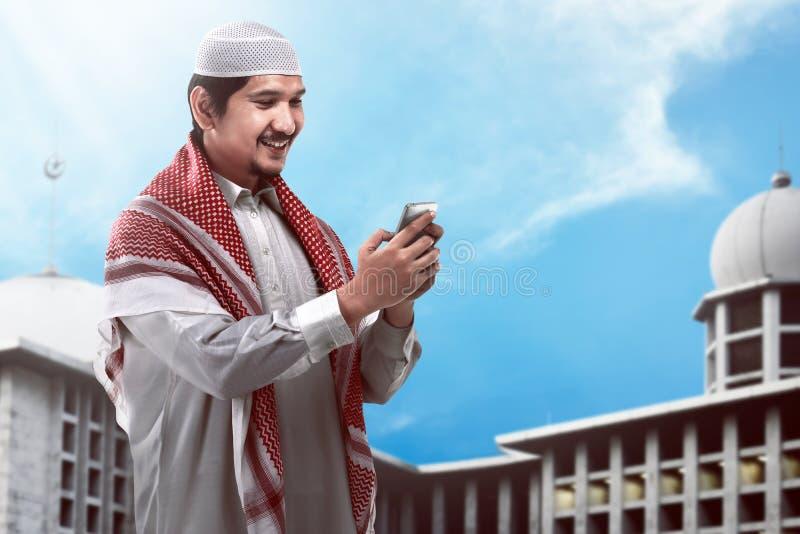 Μουσουλμανικό κινητό τηλέφωνο εκμετάλλευσης ατόμων στοκ εικόνα με δικαίωμα ελεύθερης χρήσης