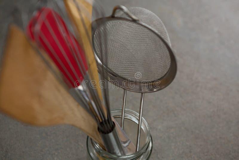 Μουστάκι, ξύλινο κουτάλι, διηθητήρας και spatula στο βάζο γυαλιού στοκ φωτογραφίες