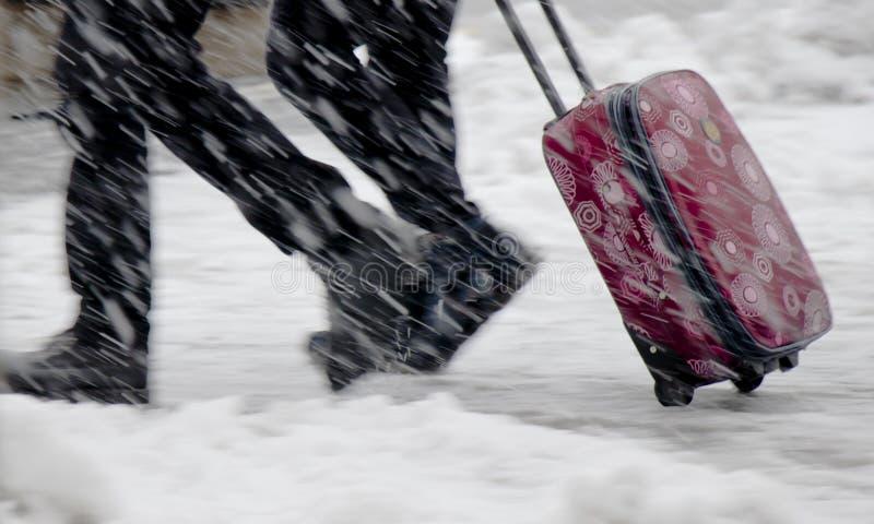 Μουτζουρωμένα πόδια δύο ανθρώπων που περπατούν γρήγορα στις βαριές χιονοπτώσεις και την κυλώντας κόκκινη βαλίτσα στοκ εικόνα με δικαίωμα ελεύθερης χρήσης