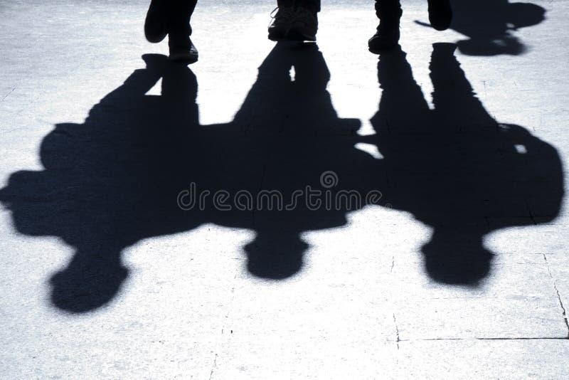 Μουτζουρωμένες σκιαγραφίες και σκιές τριών ανθρώπων που περπατούν την πόλη stre στοκ εικόνα