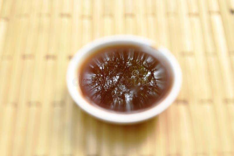 μουτζουρωμένη μαύρη σάλτσα σόγιας στο φλυτζάνι στο πιάτο μπαμπού στοκ εικόνα