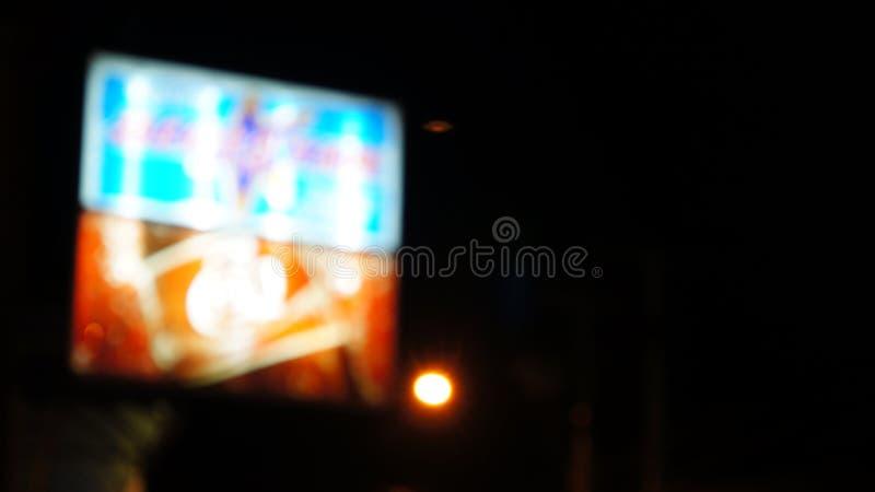 Μουτζουρωμένο αφηρημένο σημάδι νέου στο κόκκινο, το μπλε και το λευκό για τη διαφήμιση στη σκοτεινή νύχτα στοκ φωτογραφία