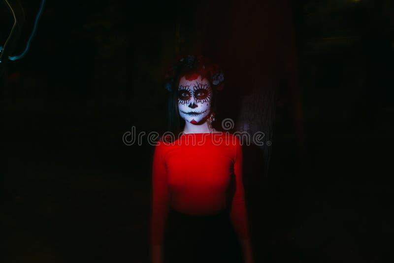 Μουτζουρωμένο σώμα και κόκκινο φανάρι με ένα χρωματισμένο πρόσωπο ενός σκελετού, ένα νεκρό zombie, στην πόλη κατά τη διάρκεια της στοκ φωτογραφία