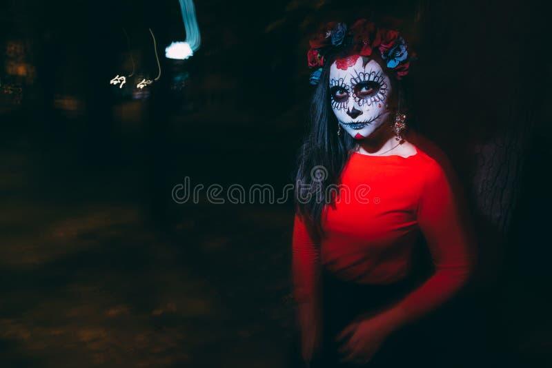 Μουτζουρωμένο σώμα και κόκκινο φανάρι με ένα χρωματισμένο πρόσωπο ενός σκελετού, ένα νεκρό zombie, στην πόλη κατά τη διάρκεια της στοκ εικόνες