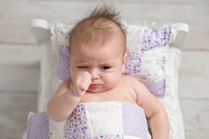 Μουτρώνοντας κοριτσάκι στο μικροσκοπικό κρεβάτι στοκ εικόνες