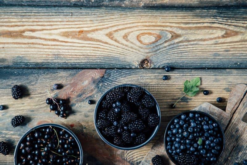 Μούρα στα κύπελλα σε ένα ξύλινο υπόβαθρο στοκ φωτογραφία