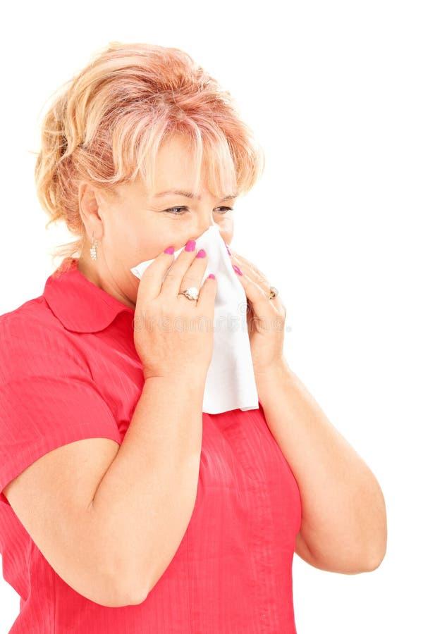 Μολυσμένη ώριμη γυναίκα που φυσά τη μύτη της στον ιστό λόγω του bein στοκ φωτογραφία