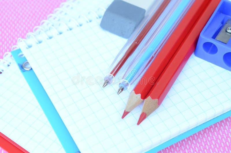 Μολύβια, στυλοί, γόμα και ξύστρα για μολύβια που βρίσκονται στα σημειωματάρια στοκ εικόνες με δικαίωμα ελεύθερης χρήσης