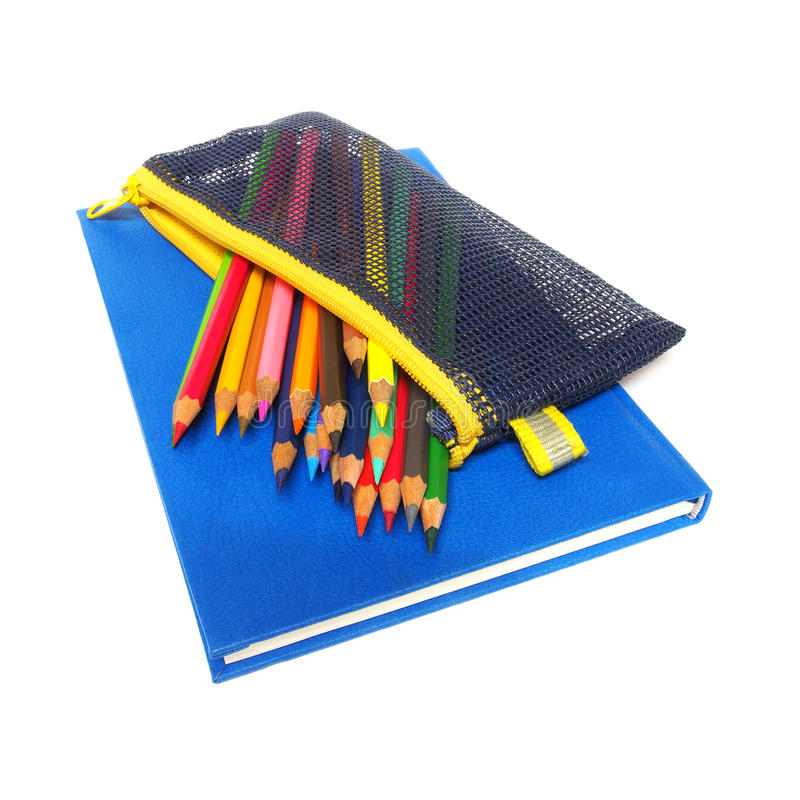 Μολύβια χρώματος και ένα μπλε βιβλίο σημειώσεων που απομονώνεται στο άσπρο υπόβαθρο στοκ εικόνες