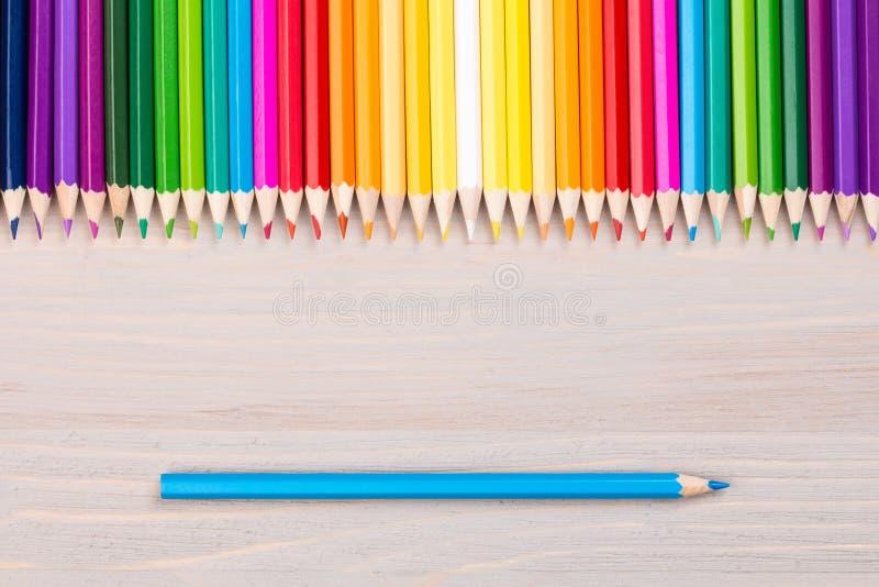 Μολύβια χρώματος στο ξύλινο υπόβαθρο με το ενιαίο μπλε μολύβι στοκ φωτογραφία