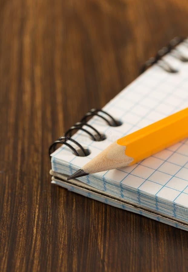 Μολύβι και ελεγχμένο σημειωματάριο στο ξύλο στοκ φωτογραφία με δικαίωμα ελεύθερης χρήσης