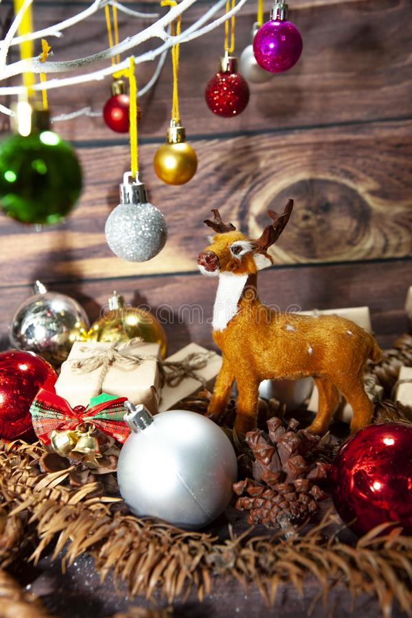 Μπάλες γεμάτα χρώματα χριστουγεννιάτικα στολίδια κρεμασμένα από χριστουγεννιάτικο δέντρο σε ξύλινο χαρτόνι στοκ εικόνα