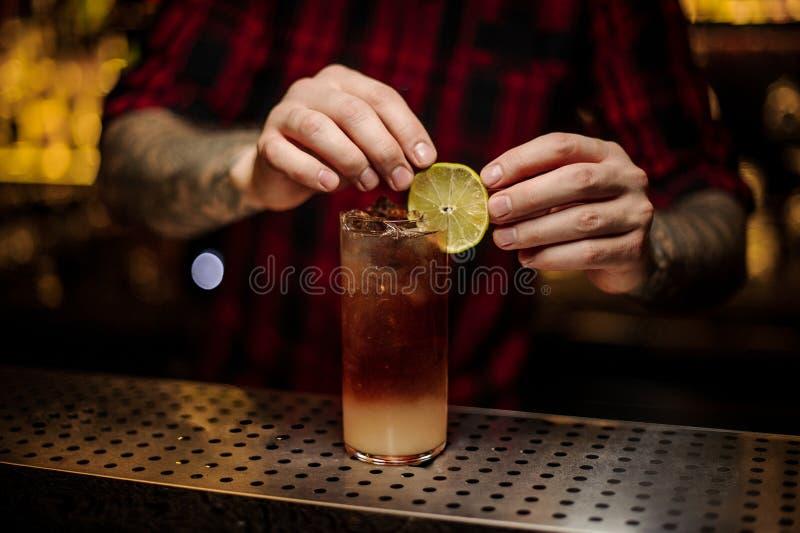Μπάρμαν που διακοσμεί το γυαλί κοκτέιλ με τον οινοπνευματώδη χυμό με μια φέτα του λεμονιού στοκ εικόνα