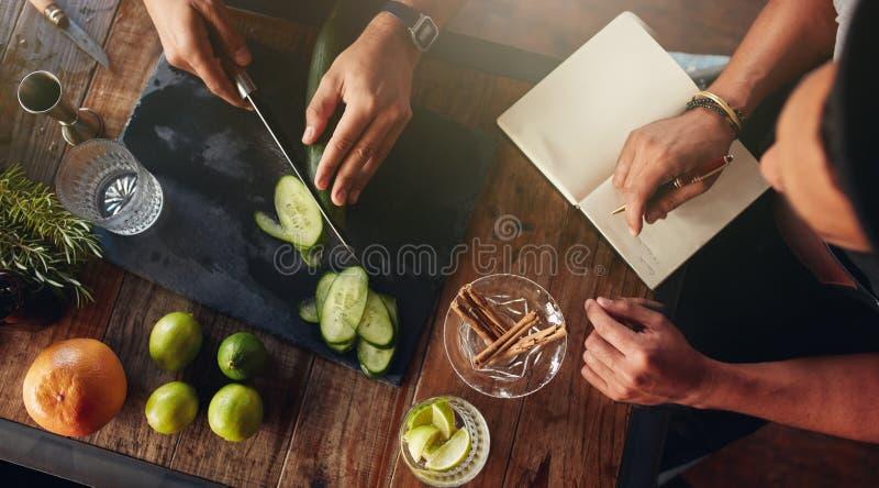 Μπάρμαν που πειραματίζονται με τη δημιουργία των νέων κοκτέιλ στοκ εικόνες